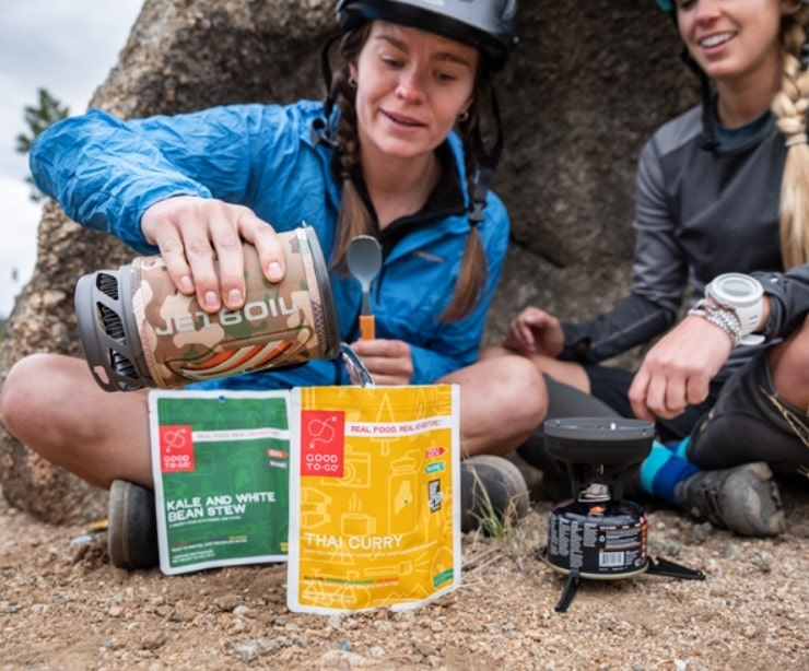 Hikers pouring a boiled water from a jetboil stove
