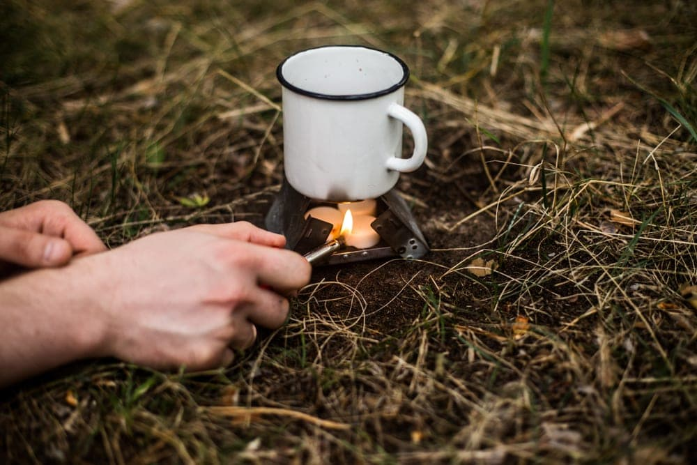 Person lighting up a solid fuel stove to boil water while camping