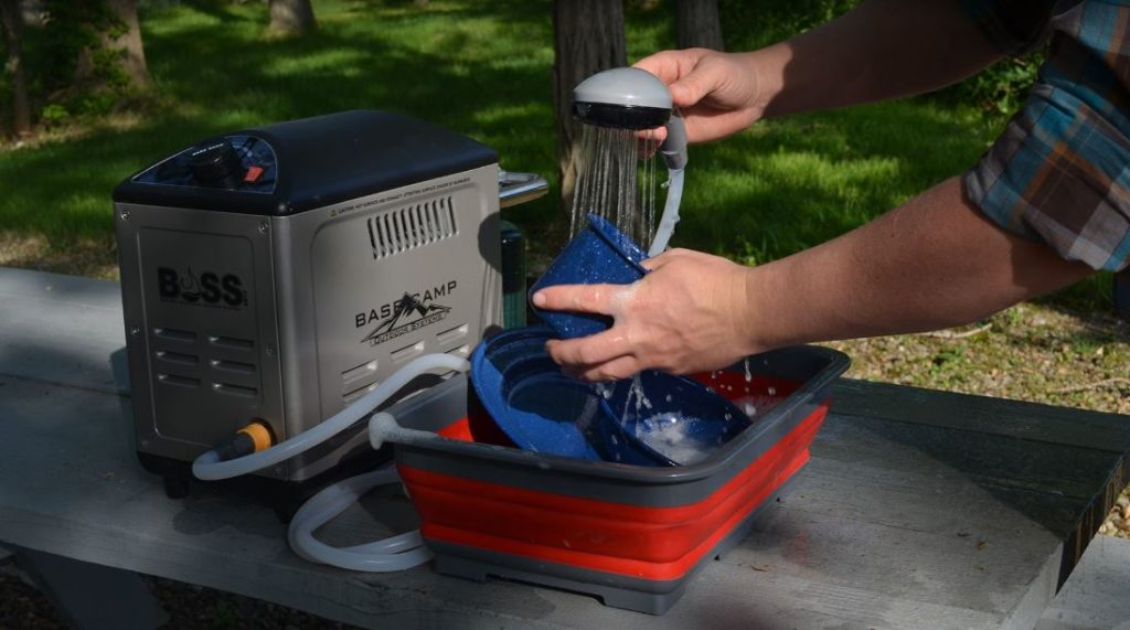 Man washing plates using a water heater while camping