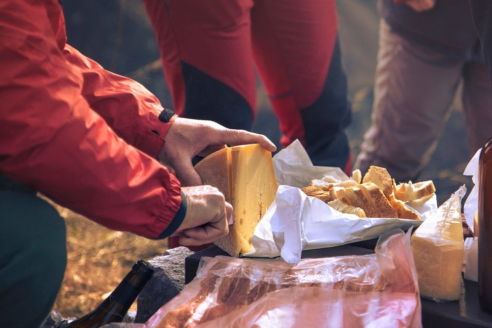 Group of campers slicing a cheese as their camping food