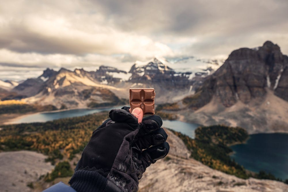 Hiker holding a chocolate bar as camping food