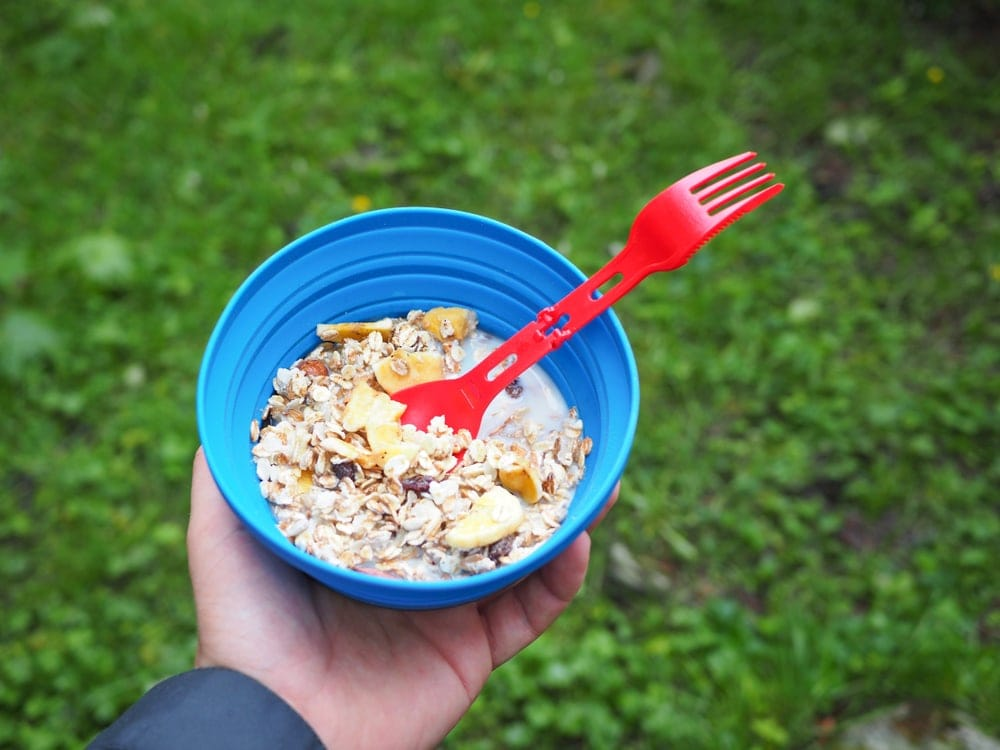 A person holding a bowl with granola as part of her camping snack