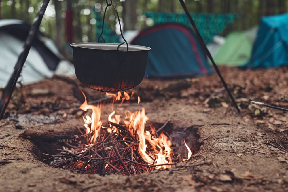 Cooking in a pot over campfire while camping