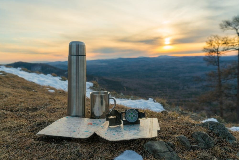 Camping thermoses and gears and map on top of the mountain