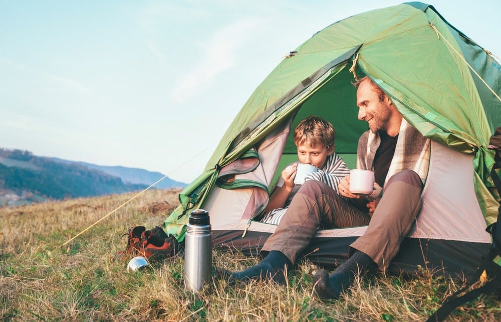 Camping thermos outside of a tent with father and son inside drinking coffee