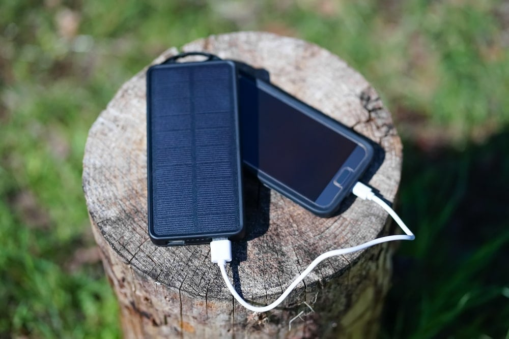 Phone connected to a solar powerbank on the woods