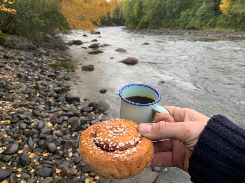 A camper holding a cup and a cinnamon as camping food