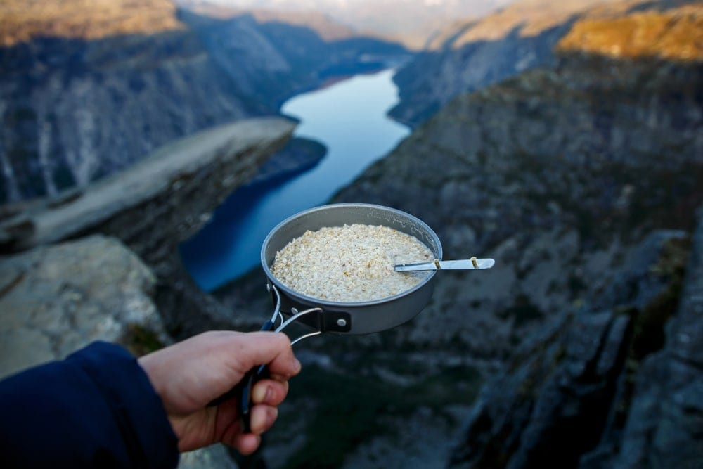 A hand holding a pan with oatmeal while camping