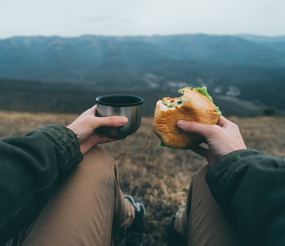 Holding a cup and a burger as camping food