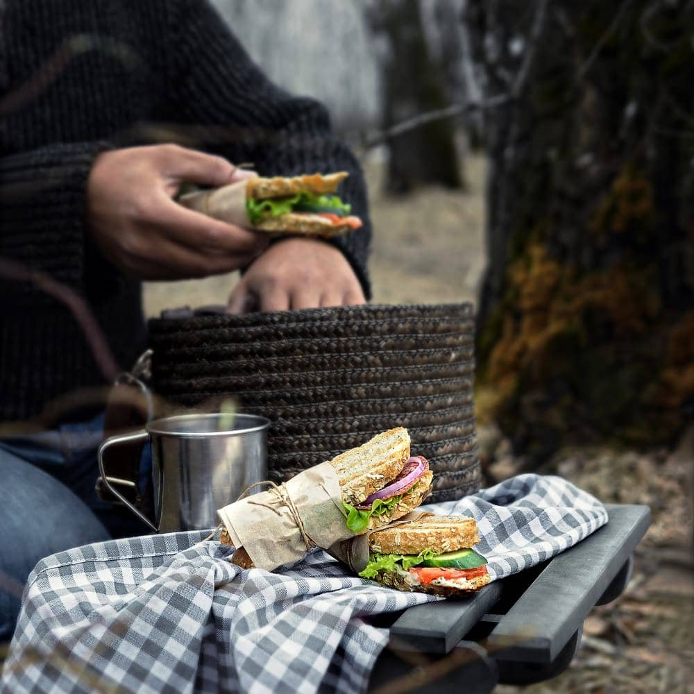 Man holding sandwich and others displayed on the table as camping food