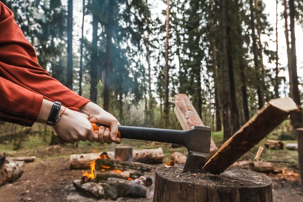 Person splitting firewood during camping