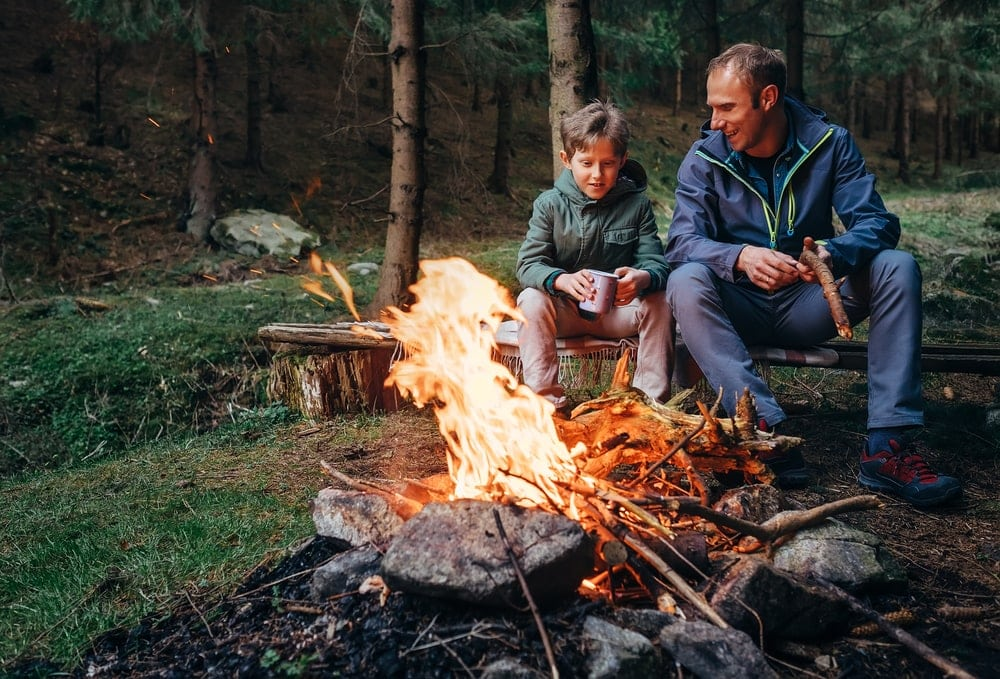 Father holding camping firewood while talking to son
