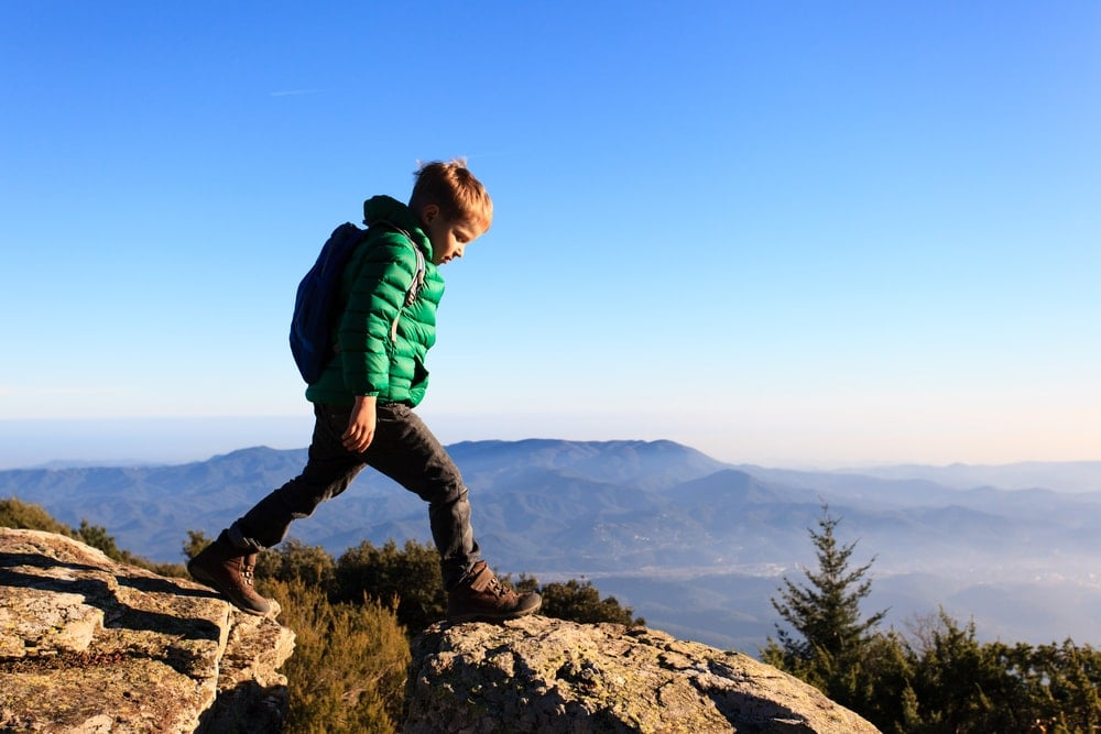 Kid hiking on rocks above the mountains