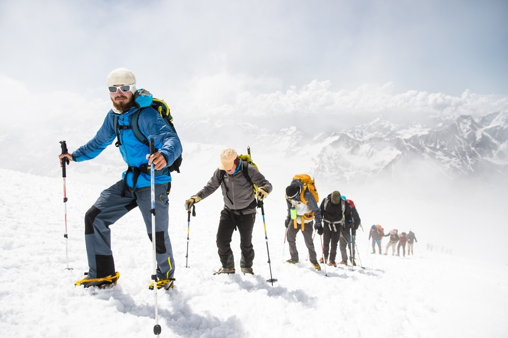 Outdoor guide leading a group of hikers on a snowy mountain