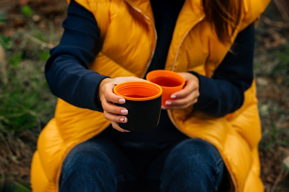 Woman holding a cup while camping