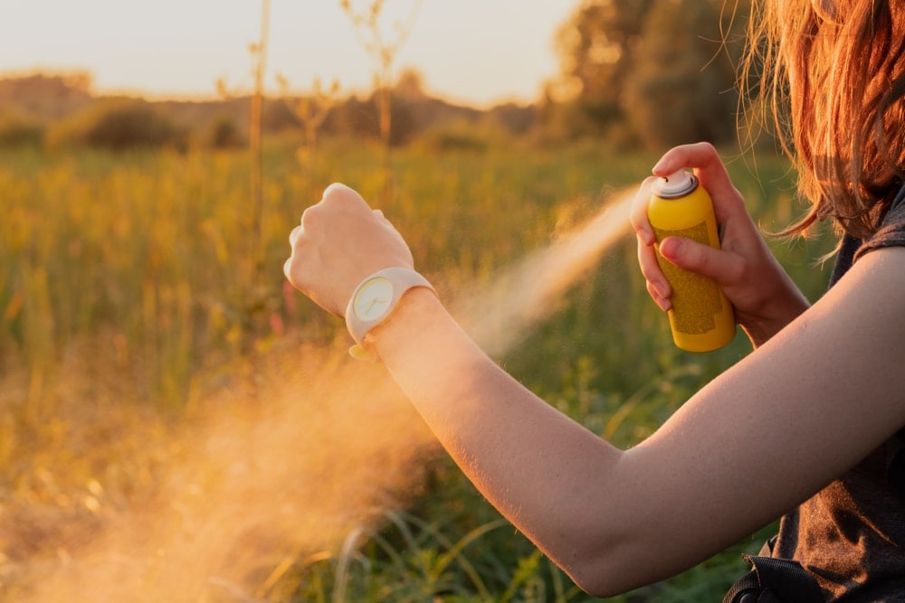 Woman spraying bug spray to her skin while camping