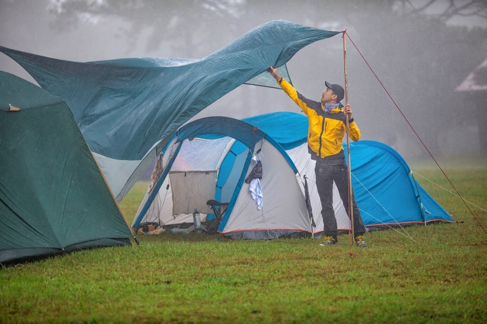 Man setting up rainfly over his camping tent while raining