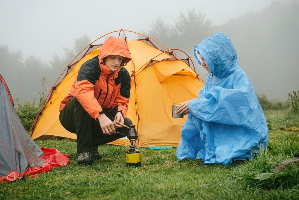 2 people boiling water with camping tent behind them