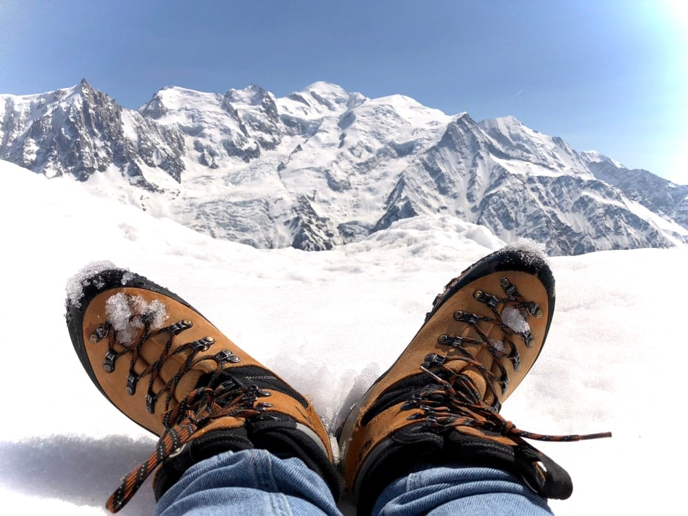 Hiking shoes touching the snow with mountain view