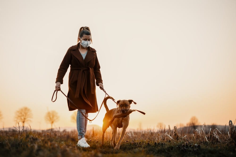 A woman holding the leash of her dog while hiking