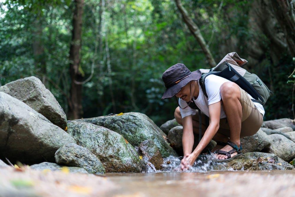 Hiker washing his hand at the river