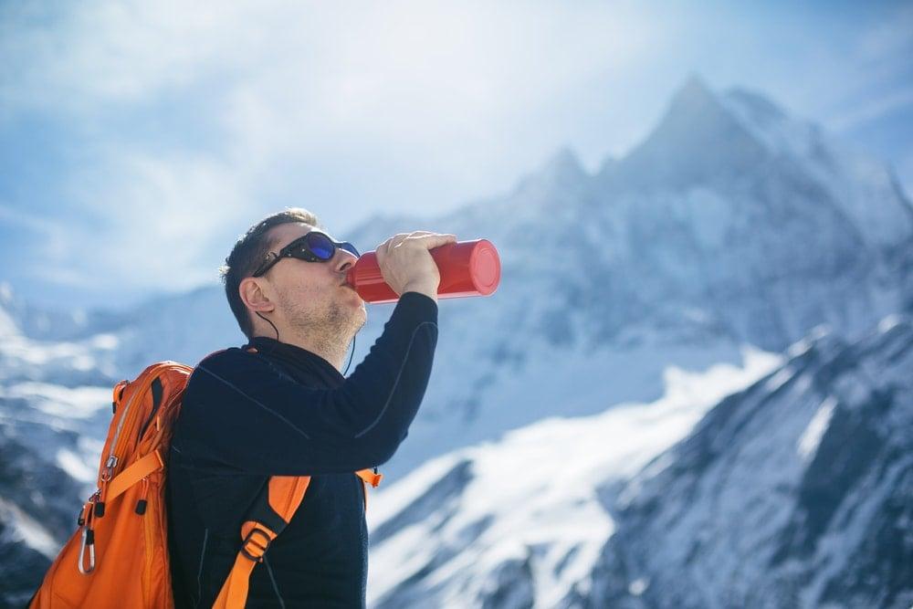 Man drinking water while hiking