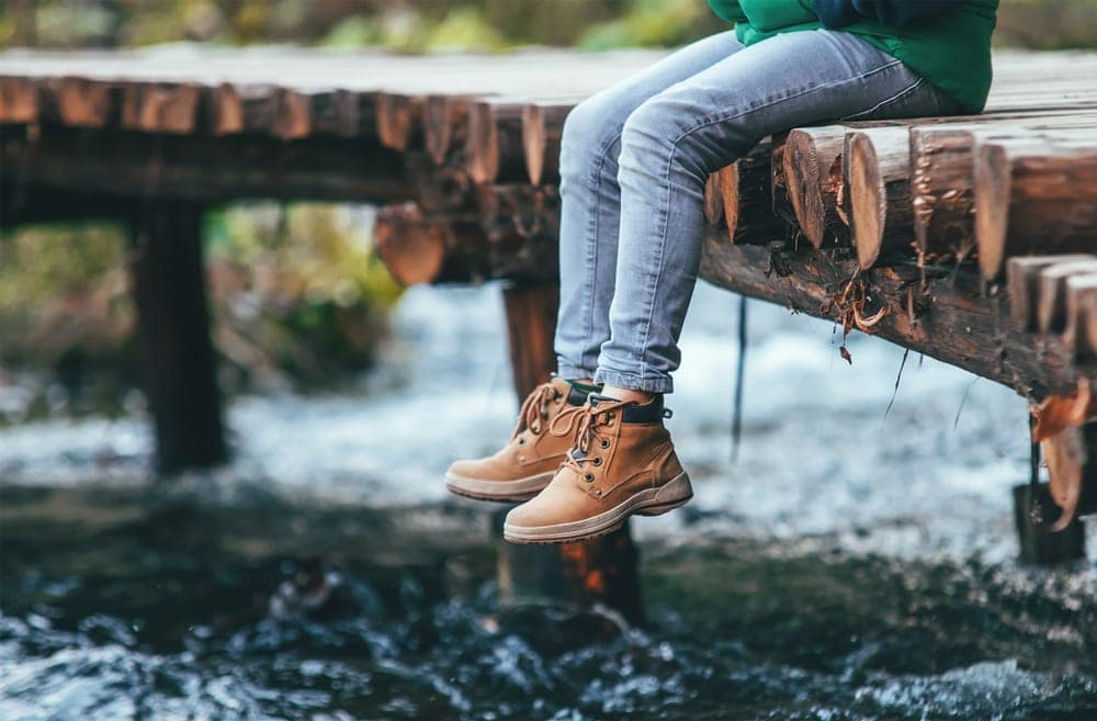 Person sitting on a bridge