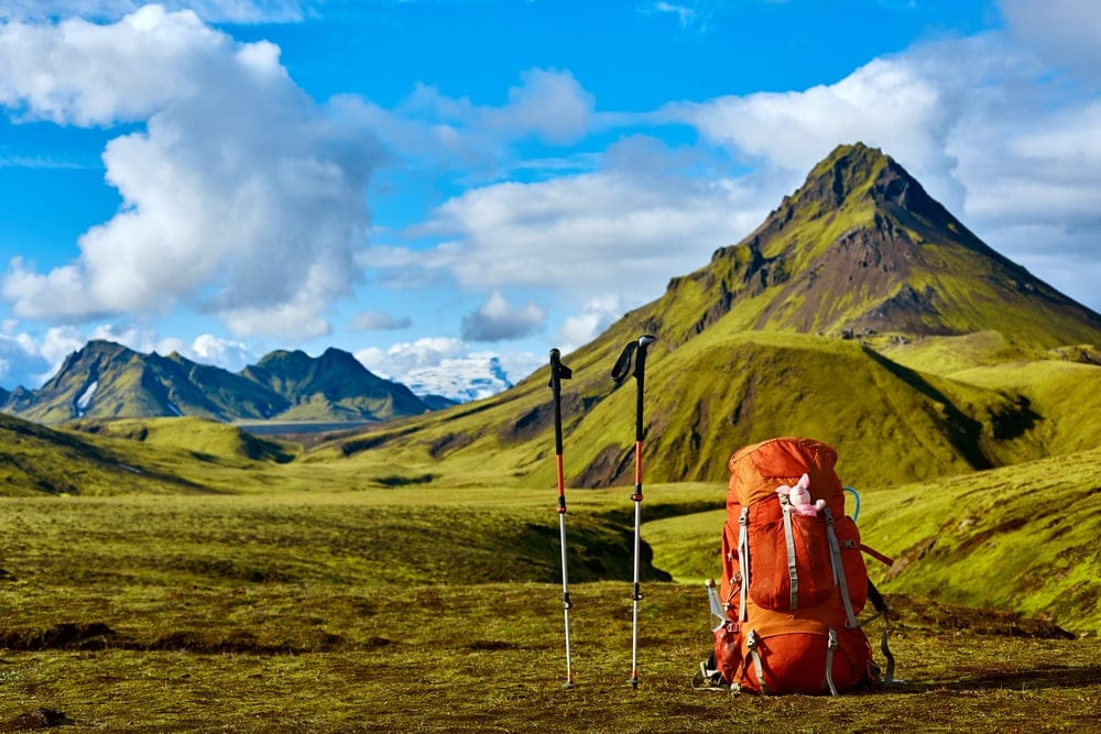 Backpack and a trekking pole with mountain at the back