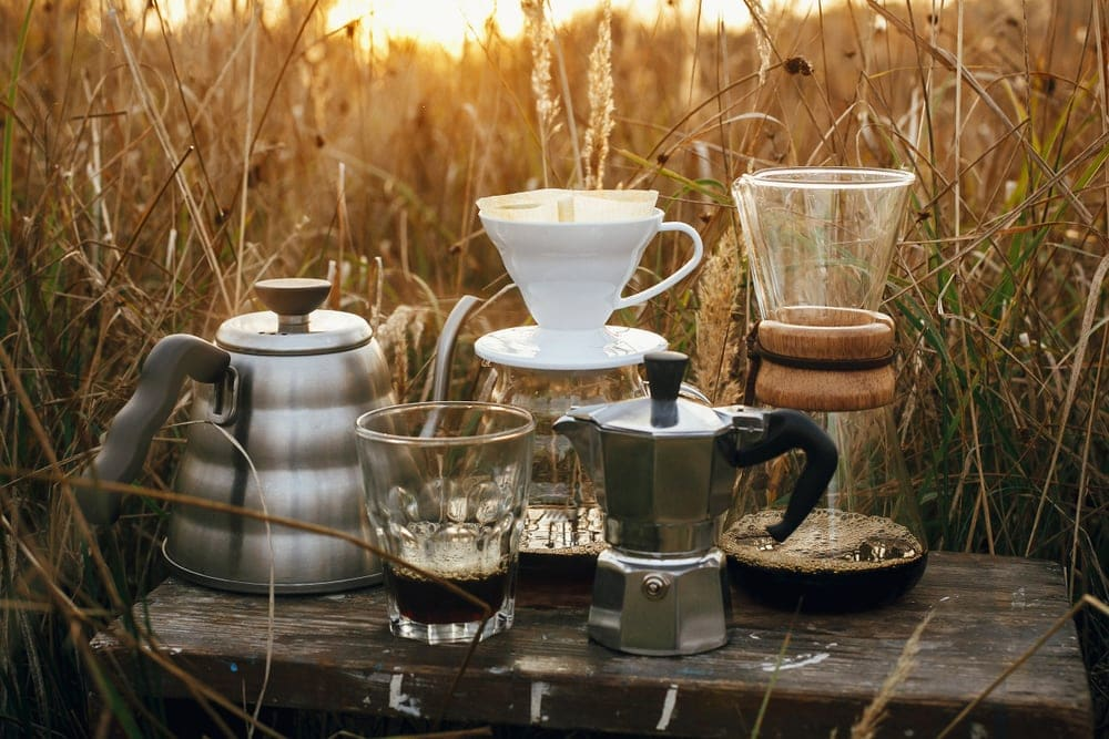 Camping coffee makers on a sunny background in rural herbs