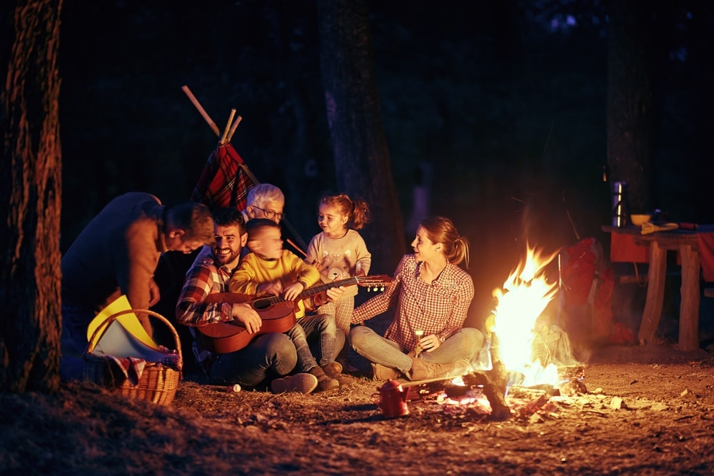 Family spending a night playing campfire games and singing