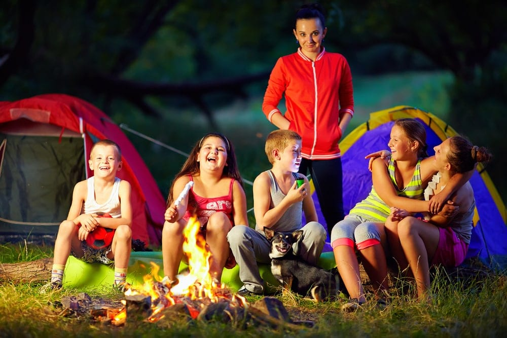 Kids laughing and talking around a campfire