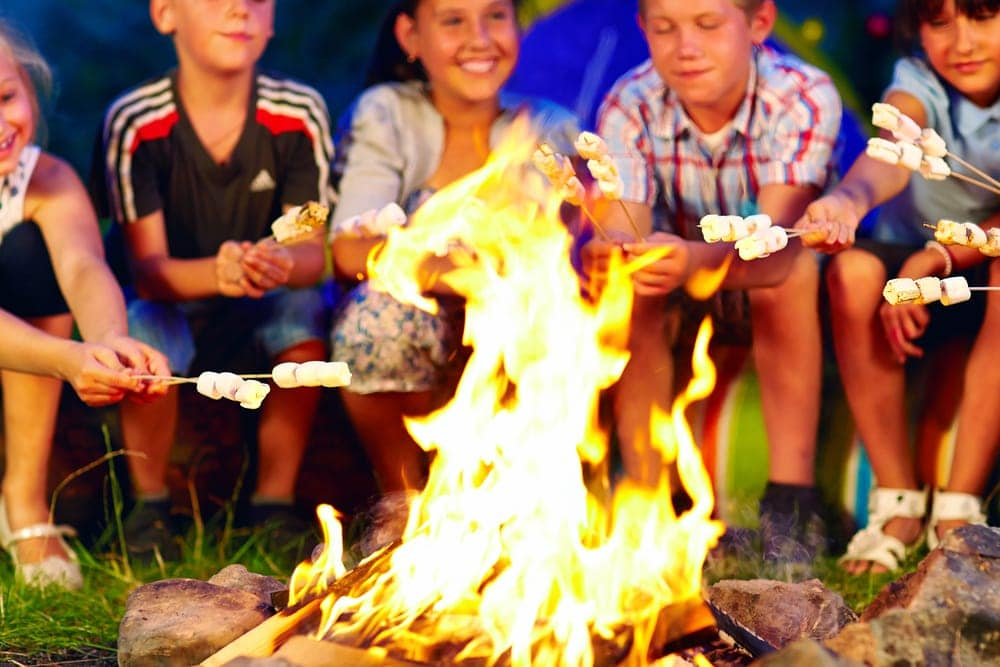 Children holding marshmallows over a campfire and playing a camping game