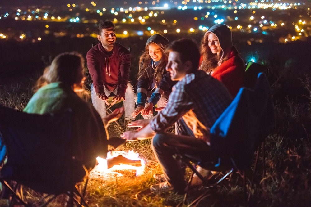 Five friends enjoying the night and playing campfire games