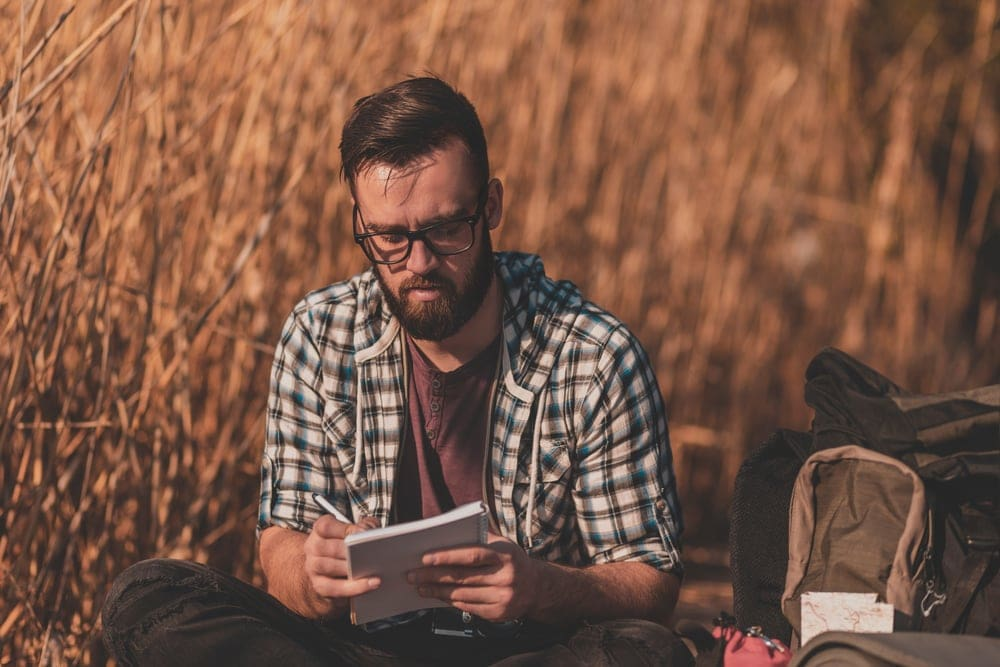 Man writing on a journal as part of a camping game