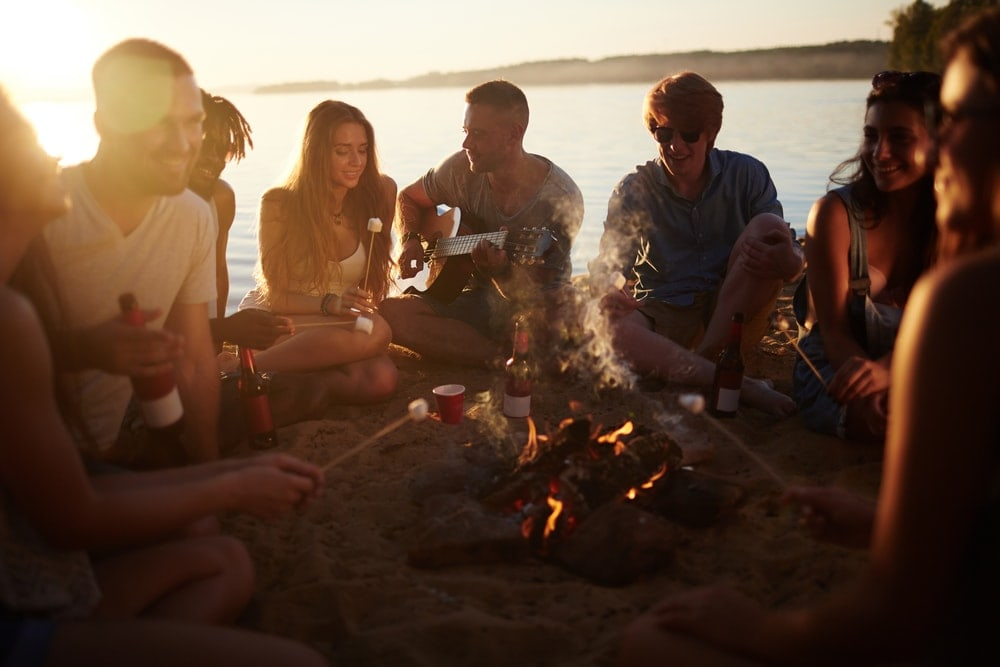 Group of friends drinking, singing and playing campfire games