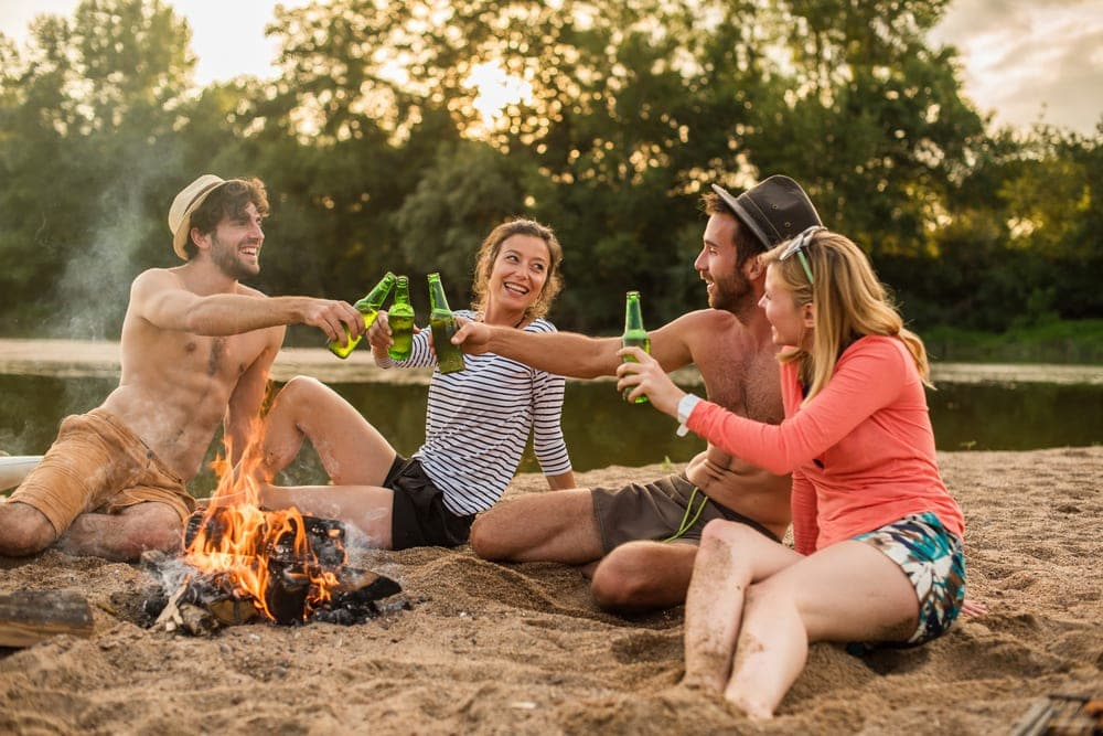 Four friends drinking and playing camping games around a campfire