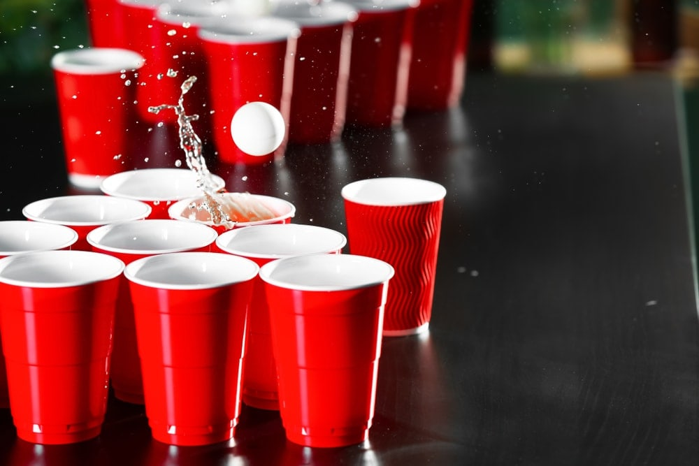 Red cups drinks and a pong ball as part of a camping game