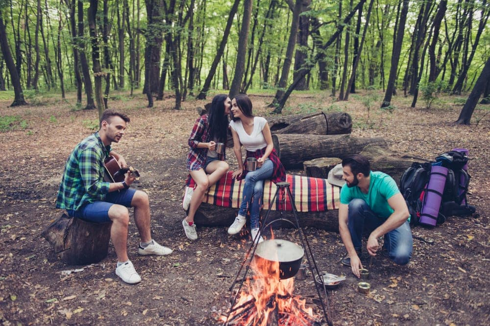 Four friends cooking, talking and playing campfire games