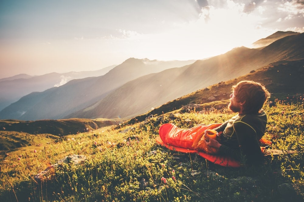 Man with sleeping bag liner watching sunrise at the top of the mountain