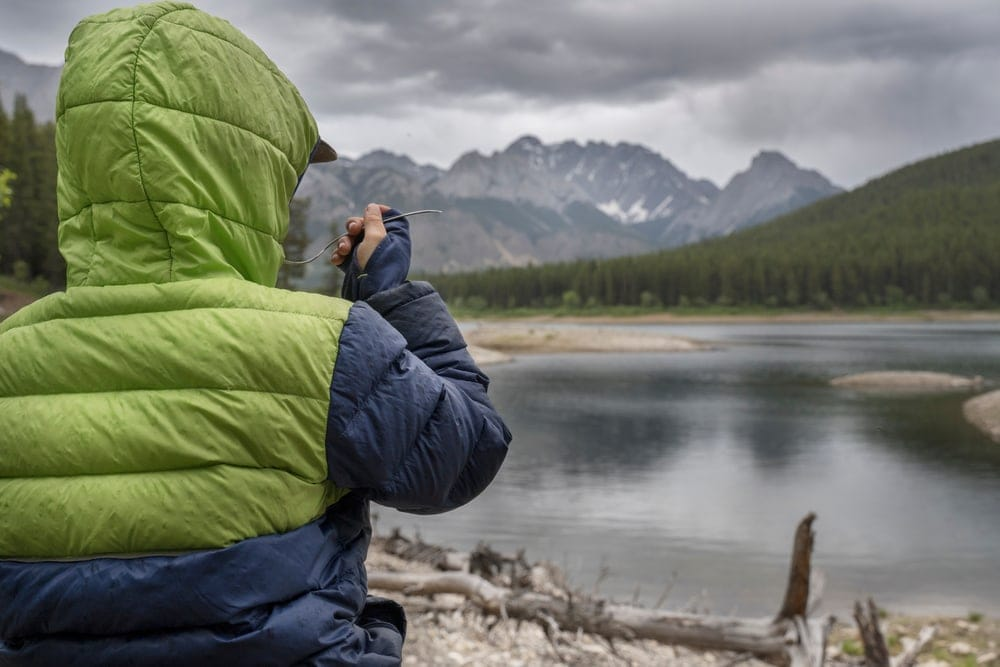 Person's back wearing a jacket looking at a lake