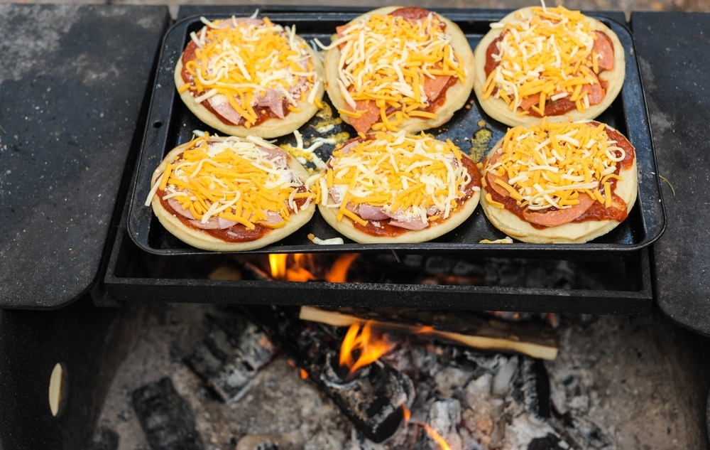 Pizzas on the pan over a campfire