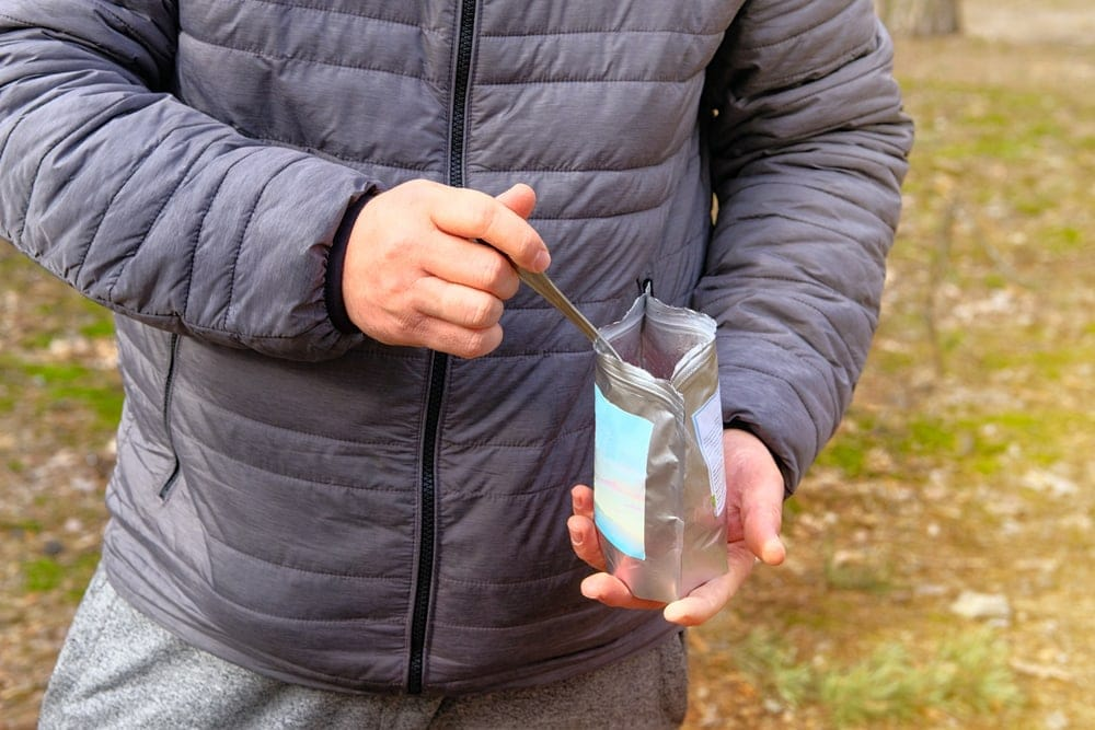 Man holding a spoon and a odor-free storage bag while camping
