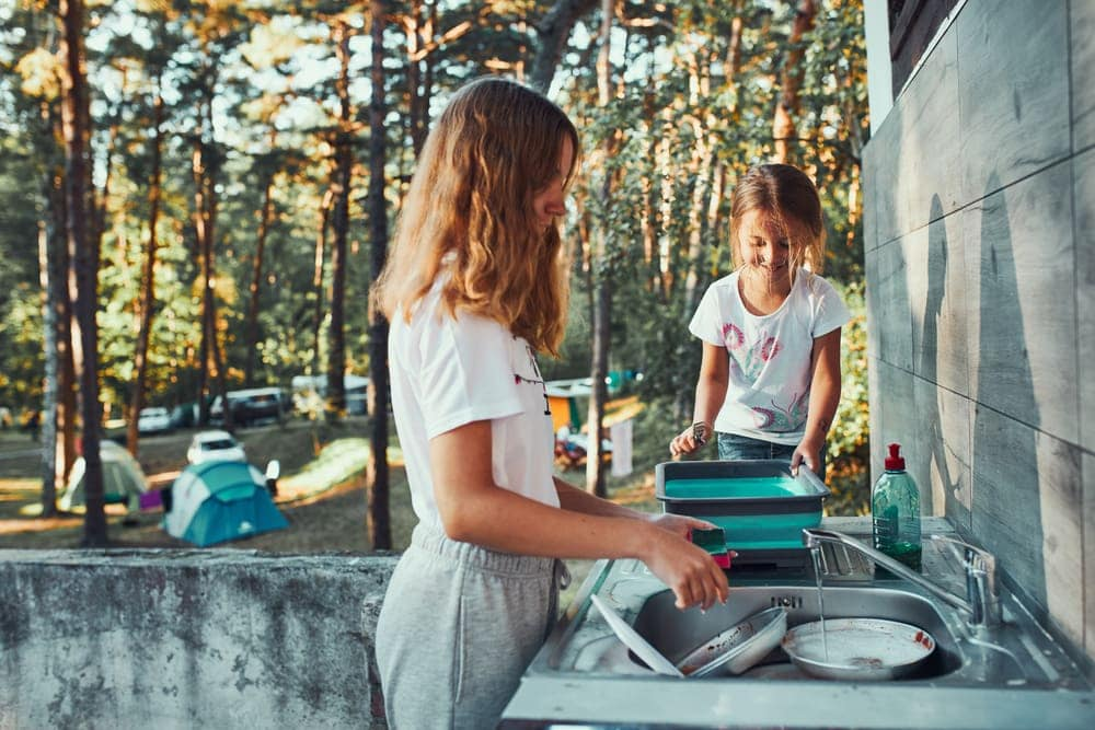Kids washing dishes in the campground to keep