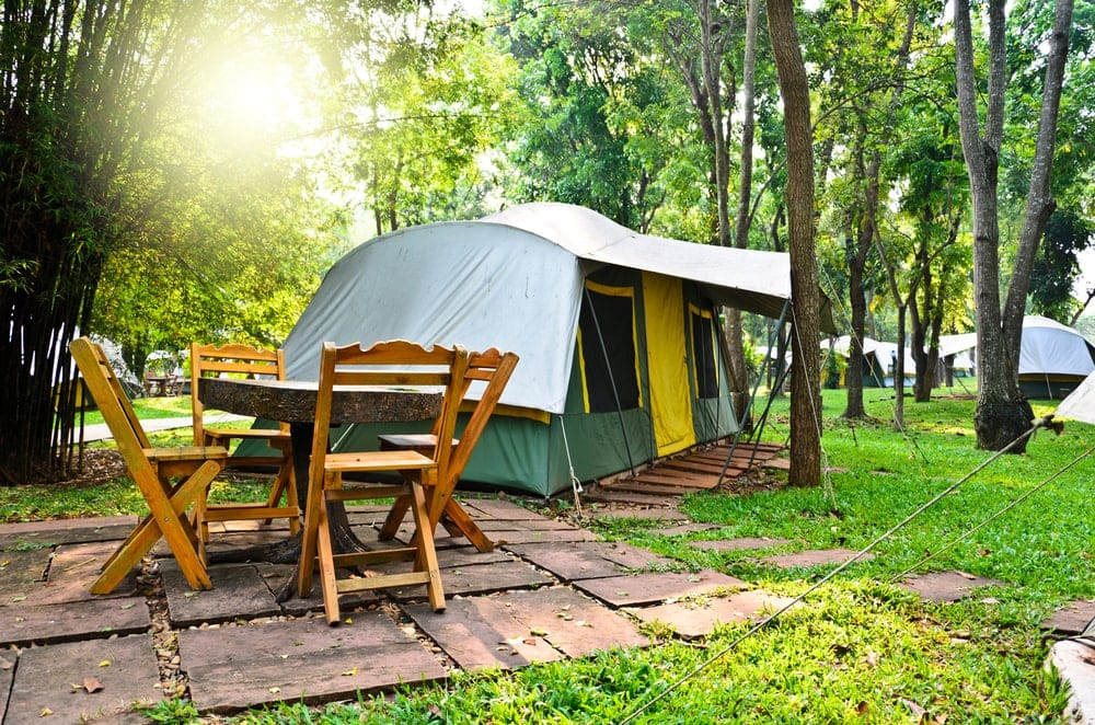 Clean campsite with table and chairs beside the tent