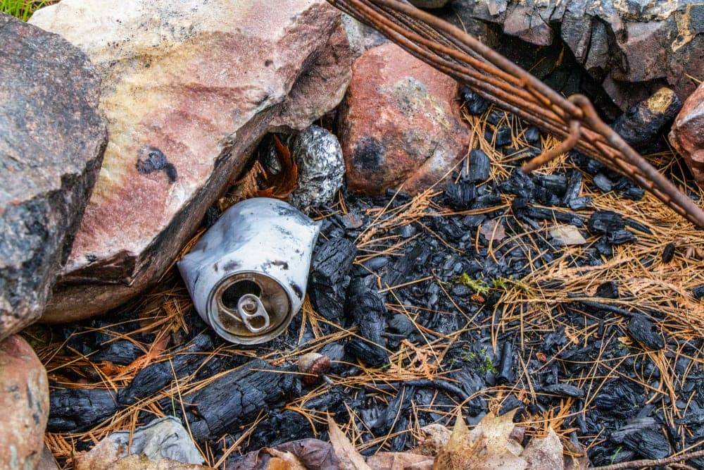 Burned drink cans under big rocks