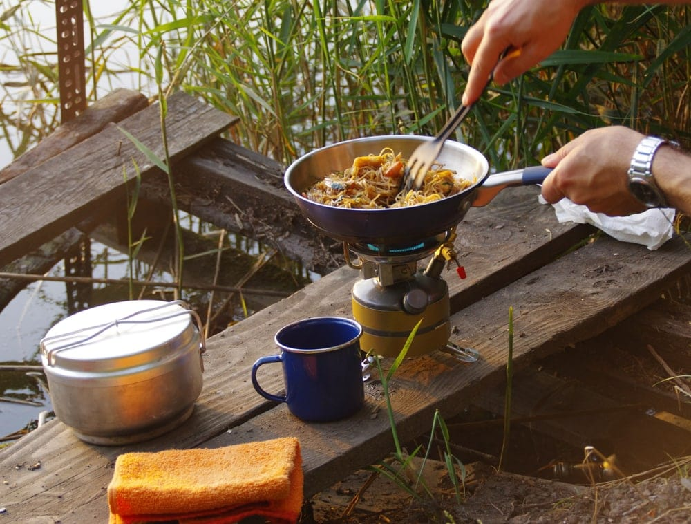 Backpacker cooking using a camp stove on the shore of the lake.