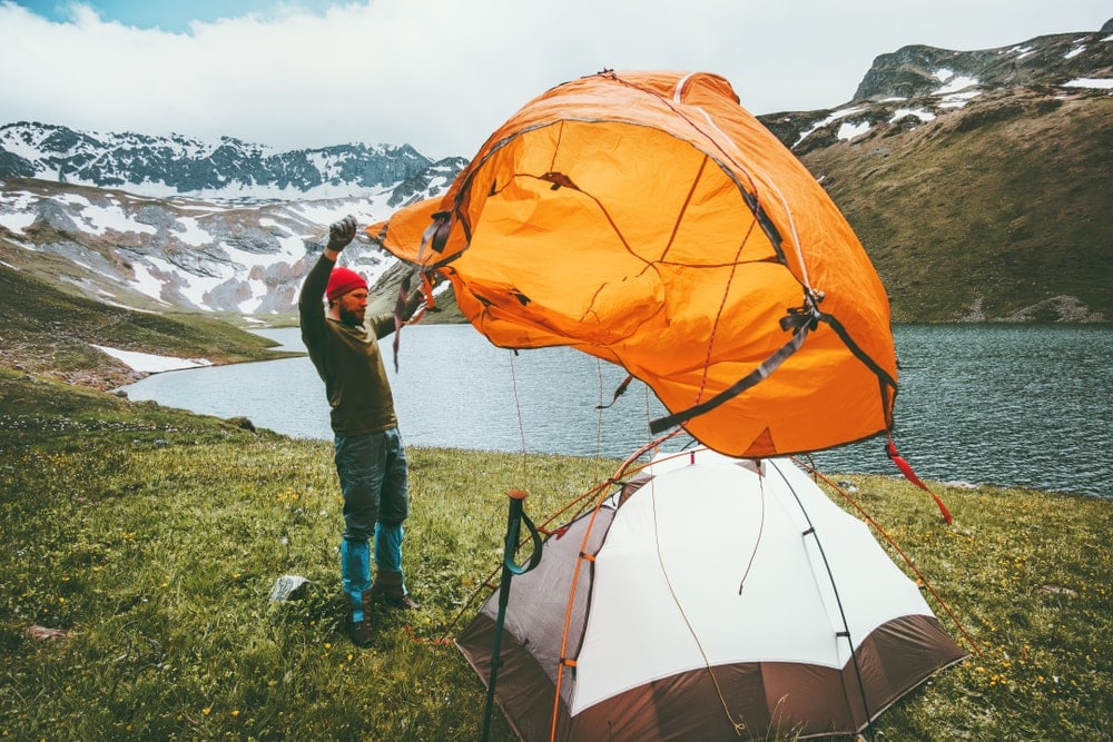Man pitching a tent during backcountry camping