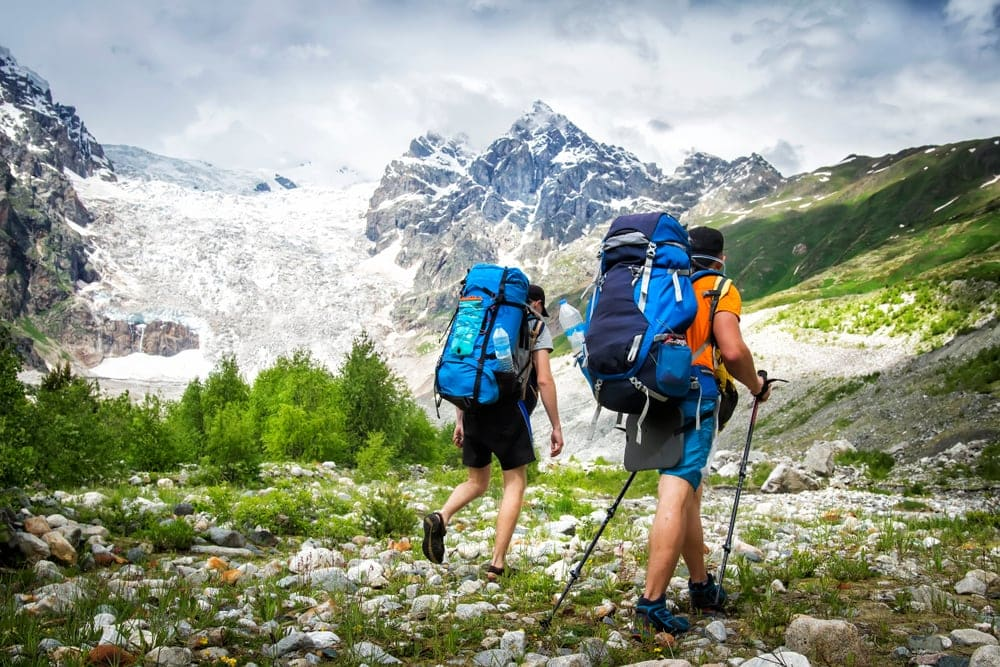 Two hikers with large backpacks in mountains.