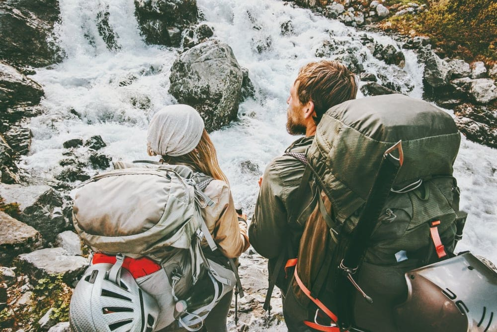 Couple with backpacks into the wild mountains