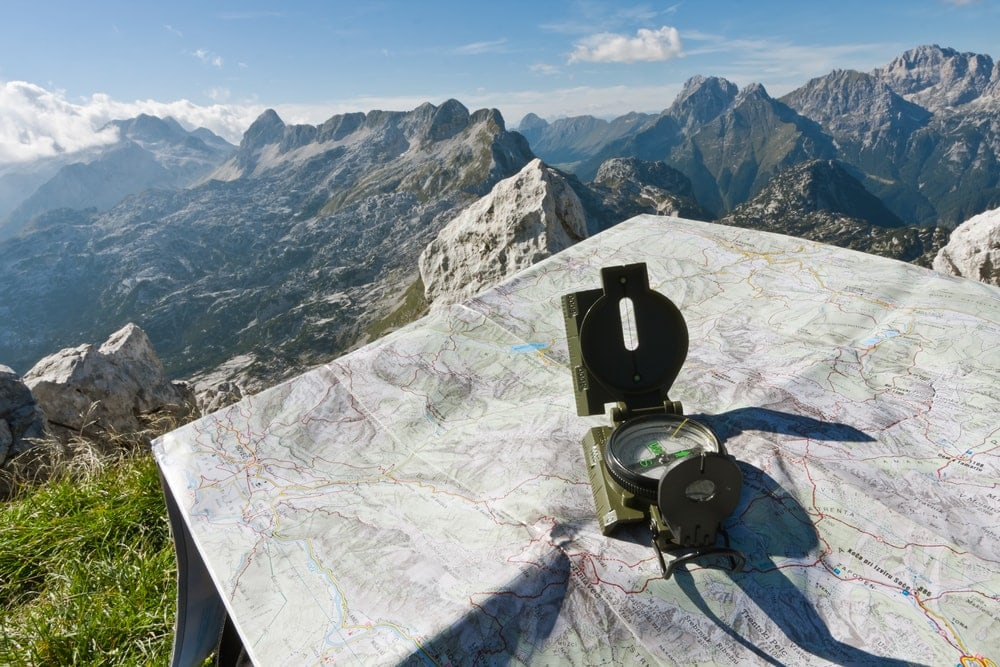 A compass and a map on the top of the mountain use for backcountry hiking